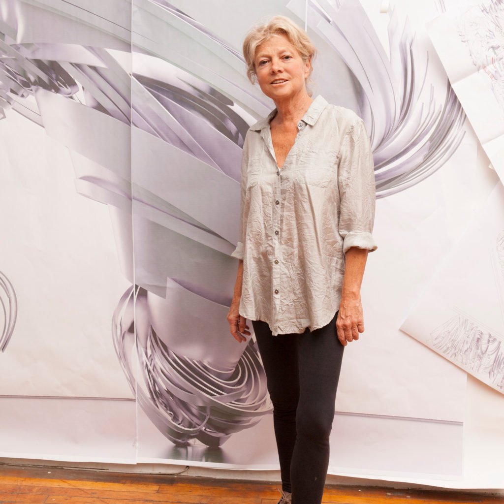 a woman stands in front of a large tornado-like drawing