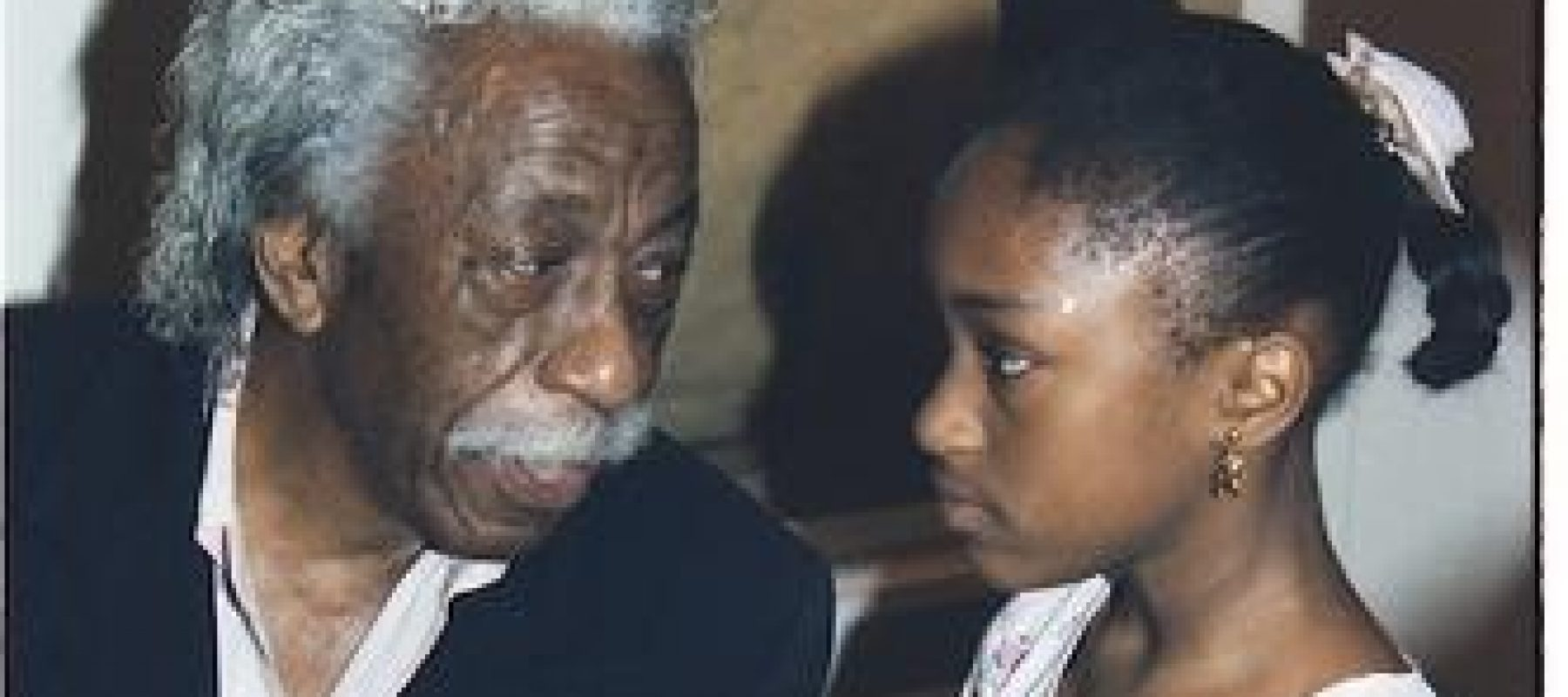 An older black man talks to a young black girl