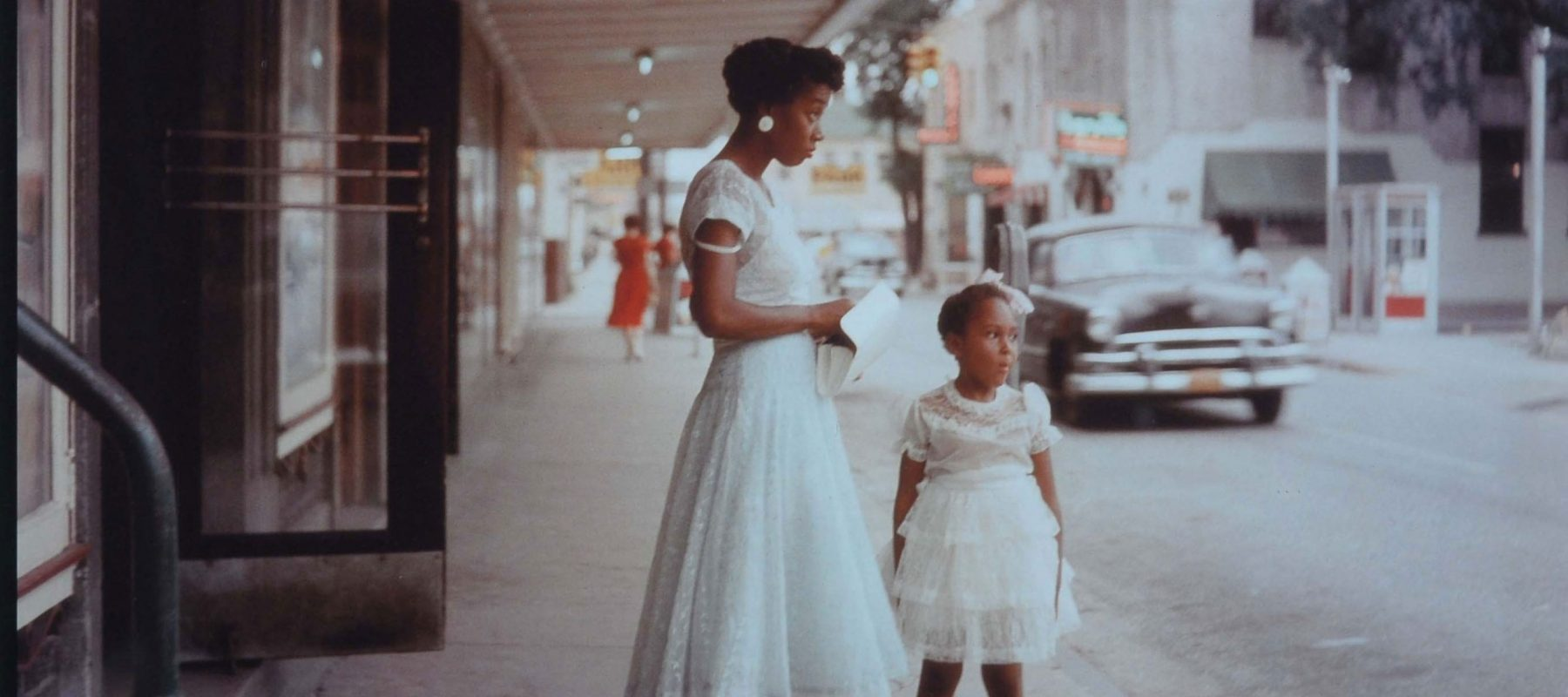 A photograph of a black mother and her girl standing below a neon sign that says 'colored entrance'