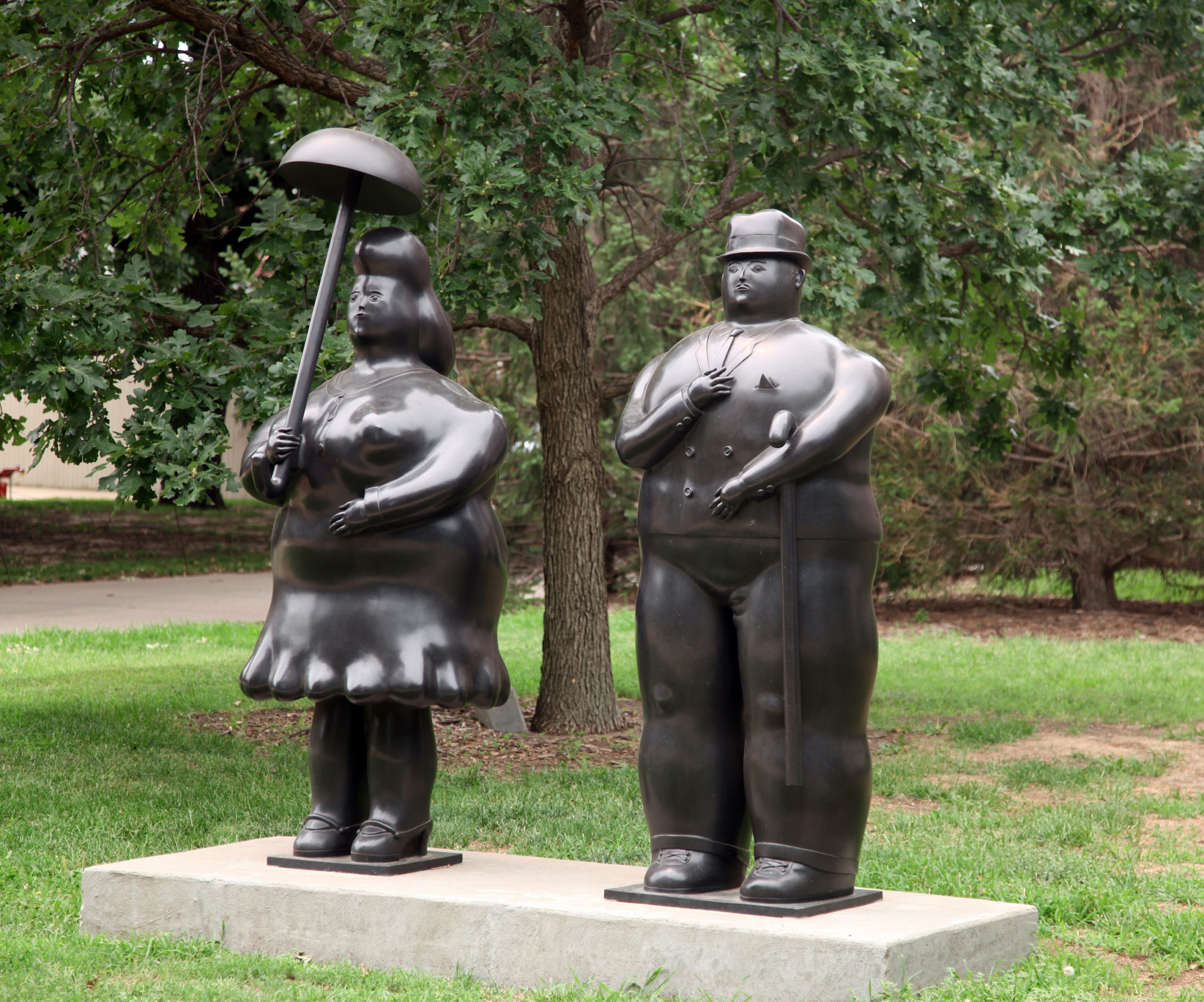 Two large statues, one of a woman with an umbrella, and the other of a man with a cane stand next to eachother