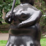 A large bronze statue of a woman with an umbrella stylized with rounded features