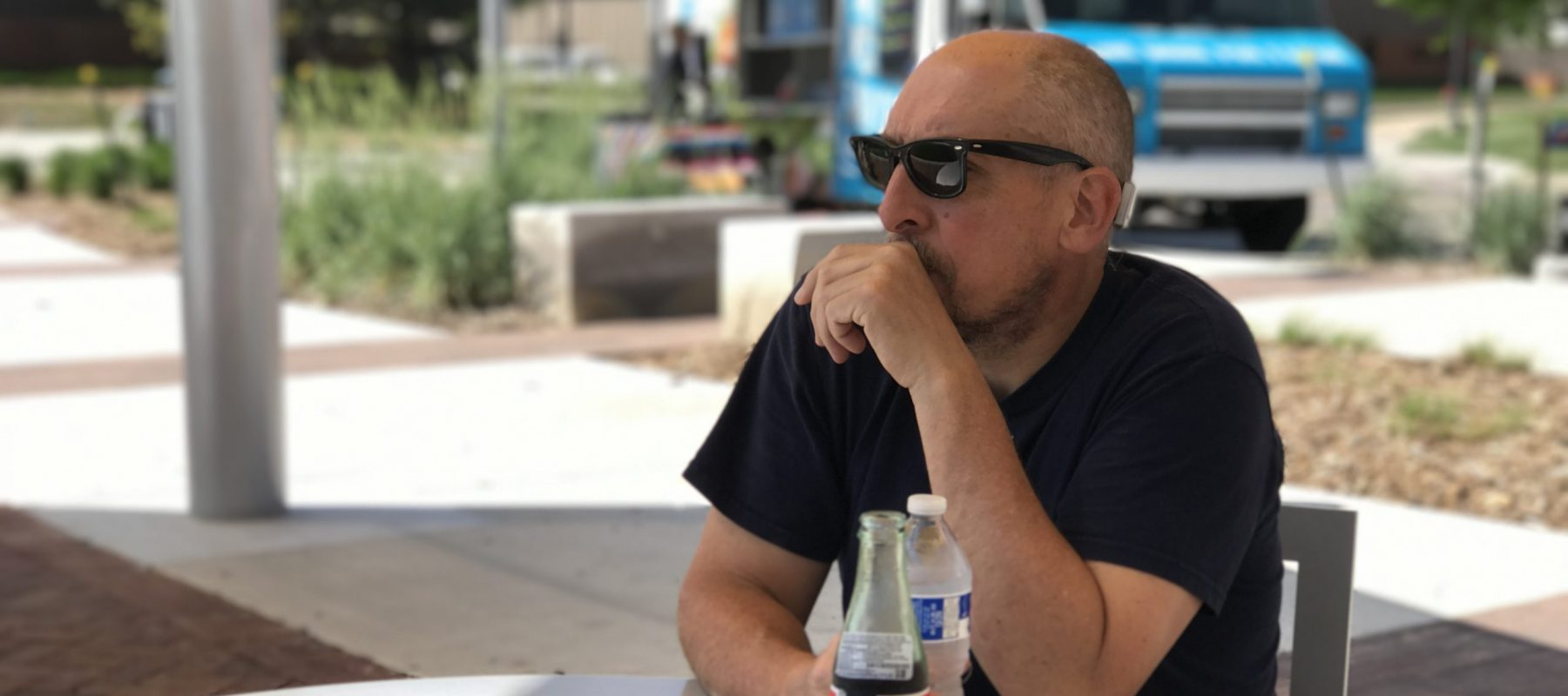 Artist Patrick Duegaw sitting at a picnic table on the WSU campus