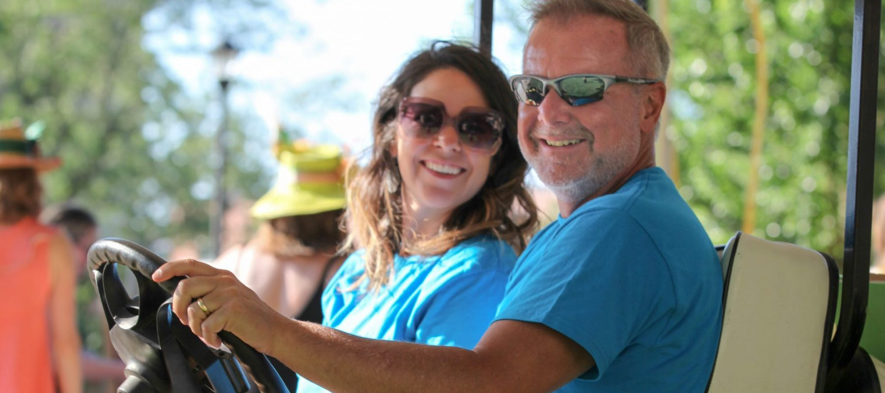 Two people in a golf cart