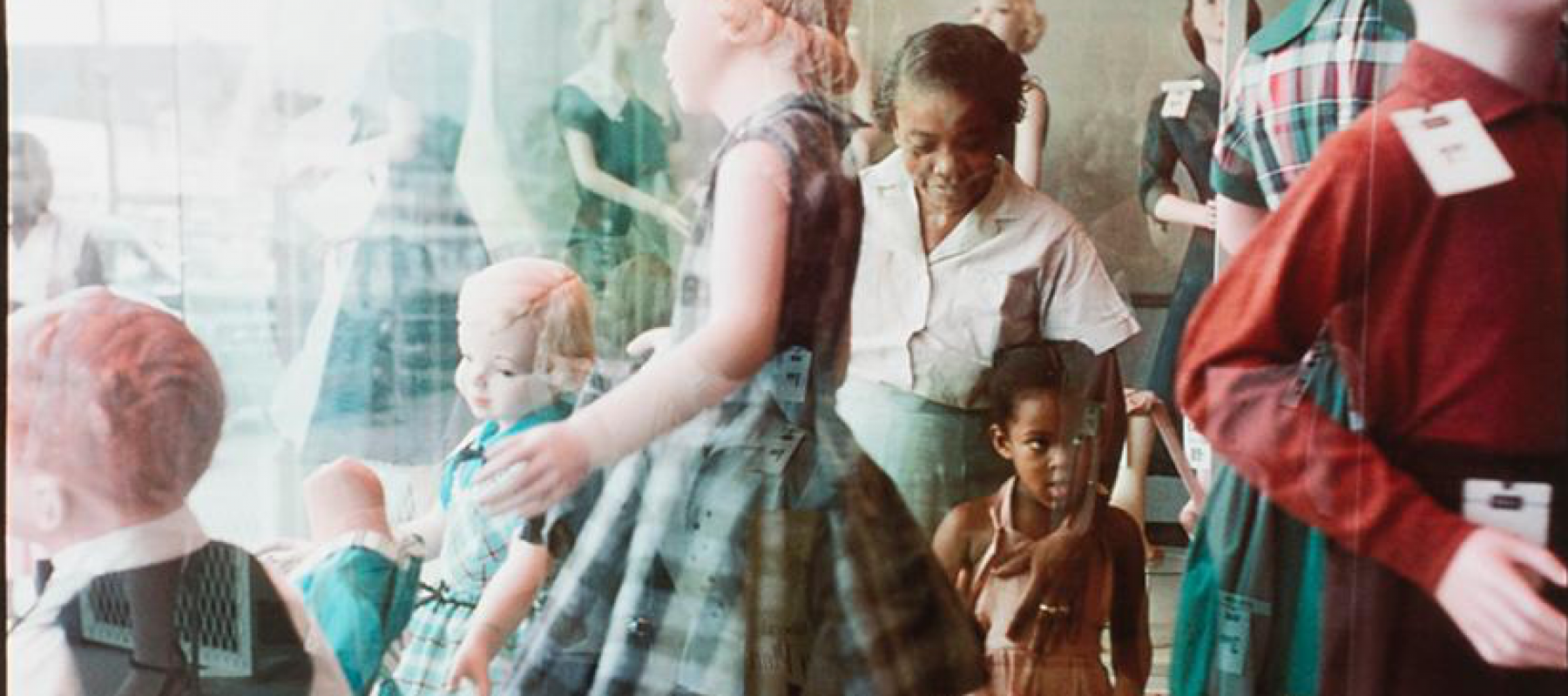 a Black girl with her grandma looks at white dolls in a 1950s shop window