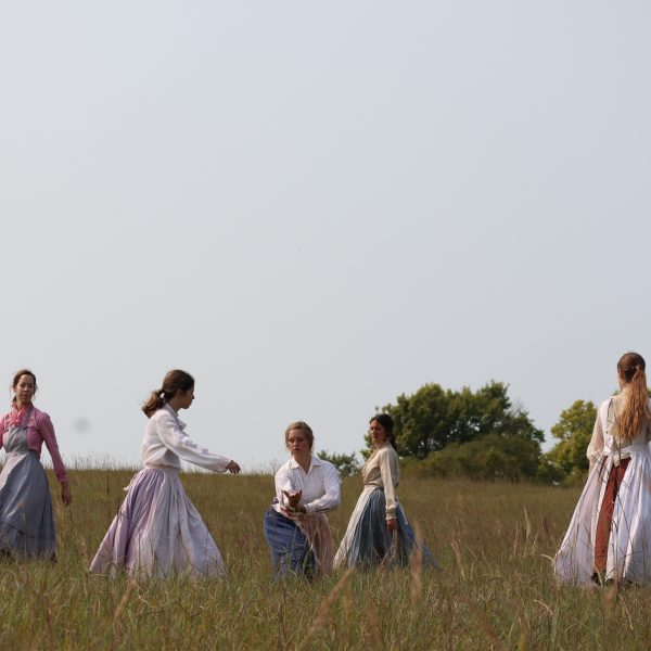 A group of people standing on top of a grass covered field