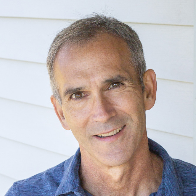 Michael Parker wearing a blue shirt and smiling at the camera